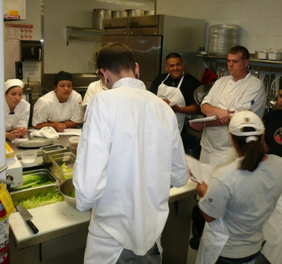 Chef Bland instructing the staff on salad plating